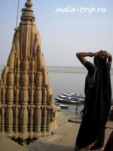 Женщина в черном сари, смотрящая на древний храм