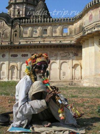 Дедушка играет на дудке перед храмом