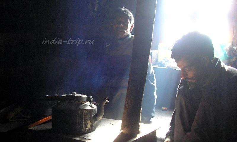 Хозяин и проводник возле печки, на которой стоит чайник