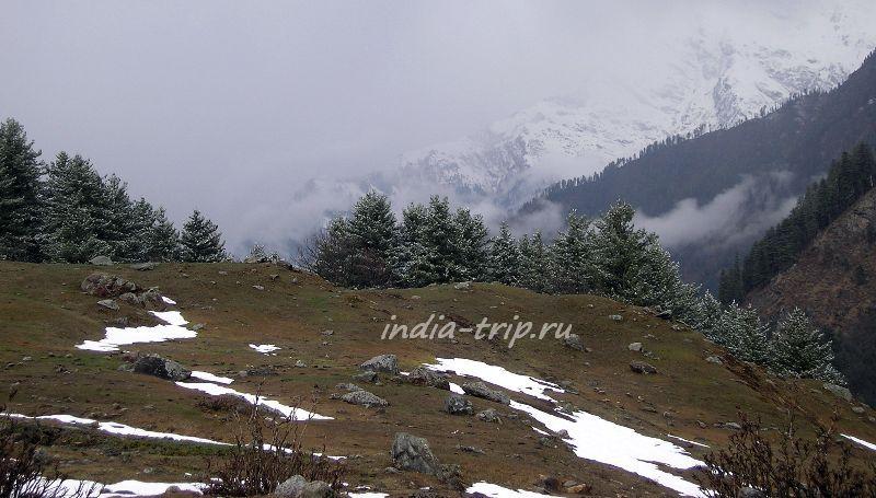 Островки снега на фоне заснеженных гор