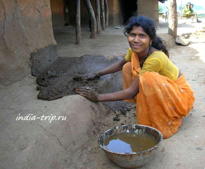 Девушка обмазывает жилище смесью с коровьим навозом